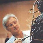 Mit dem Wissen, wie die flüssige Bronze später fließen soll, werden die Gußkanäle angebracht.